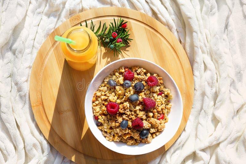 Vista superior no café da manhã saudável com granola e bagas na bacia branca e juce alaranjado fresco na bandeja de madeira redon imagens de stock royalty free