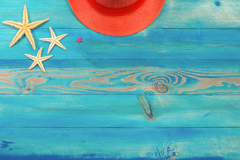 Vista superior no chapéu e na estrela do mar corais de vida da cor na textura de madeira pintada azul do vintage Configura??o lis imagens de stock