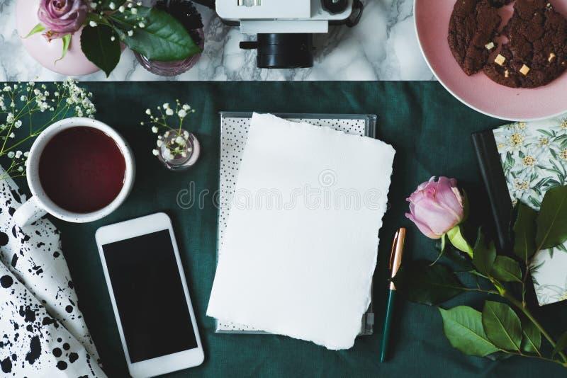 Vista superior no modelo do papel e do smartphone na tabela com rosas e a xícara de café cor-de-rosa imagem de stock