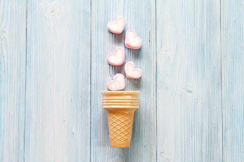 Vista superior o endecha plana del cono de las melcochas de la forma del corazón y de helado en fondo de madera azul con el espac imágenes de archivo libres de regalías