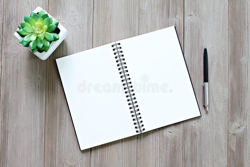 Vista superior o endecha plana del cuaderno abierto con las páginas en blanco y de la pluma en la tabla del escritorio de oficina foto de archivo libre de regalías