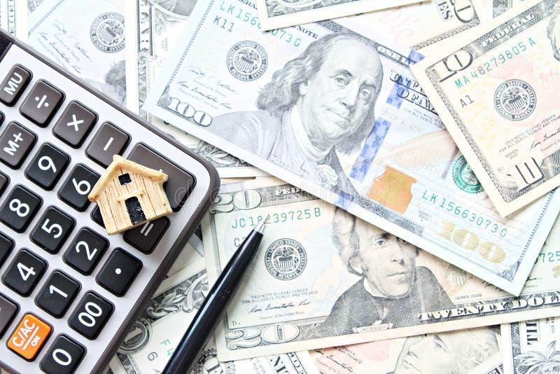Vista superior o endecha plana del modelo, de la calculadora y de la pluma de la casa de madera en el dinero americano del efecti fotografía de archivo