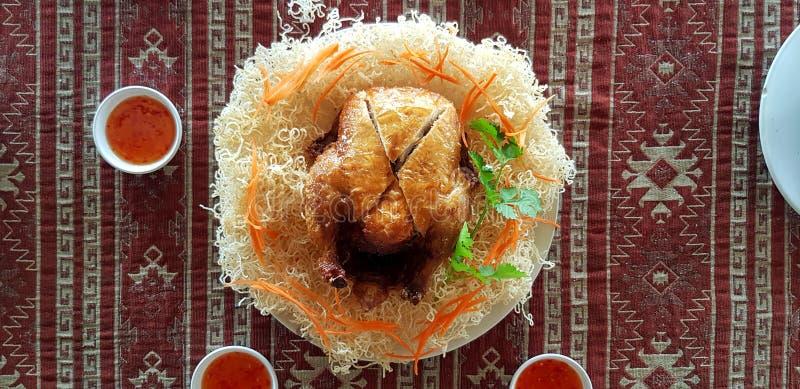 Vista superior o endecha plana del top entero del pollo asado en los tallarines blancos fritos con la zanahoria cortada, el coria imagen de archivo