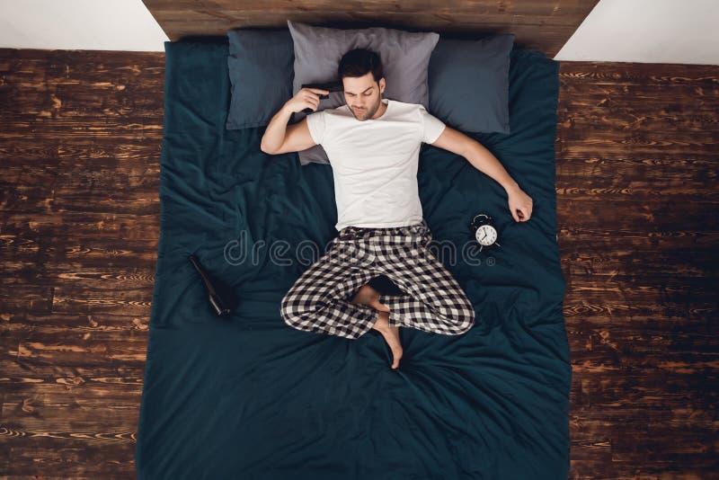 Vista superior O homem adulto encontra-se na cama ao lado do despertador e da garrafa do vinho, unindo a arma ao templo imagem de stock