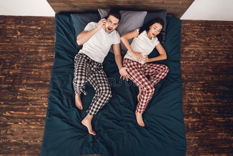 Vista superior O homem alarmado nos pijamas está soando o telefone, ao lado da menina bonita que dá o nascimento fotos de stock royalty free
