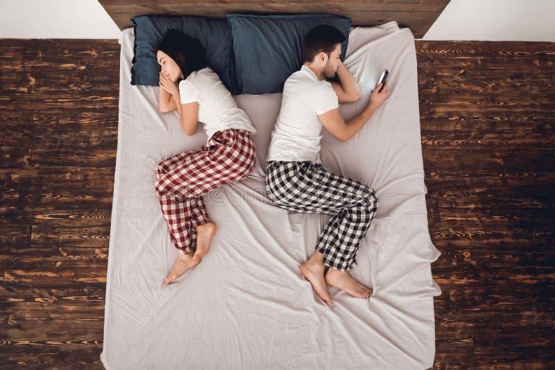 Vista superior O homem considerável adulto olha a tela do telefone ao lado da mulher de sono no sofá fotografia de stock royalty free