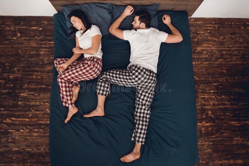 Vista superior O par novo está dormindo junto na cama grande com folha azul fotografia de stock royalty free