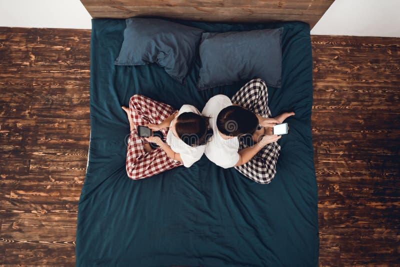 Vista superior O par novo nos pijamas senta-se na cama de volta a traseiro e a olhar fixamente em smartphones fotos de stock royalty free
