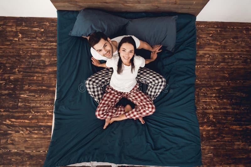 Vista superior O par novo nos pijamas senta-se na cama, pés dobrados junto e olha-se acima foto de stock royalty free