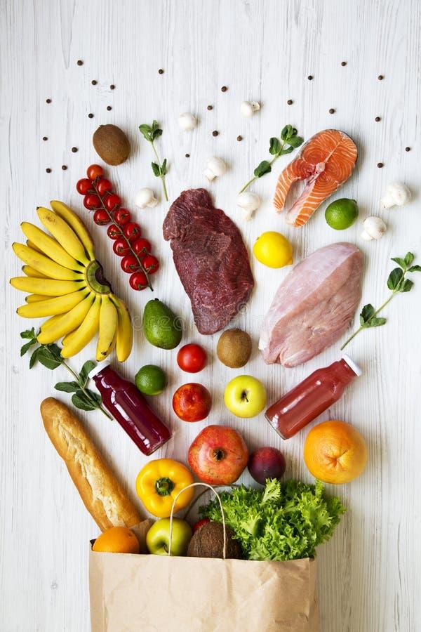 Vista superior, saco de papel de vário alimento natural Comer saudável Fundo de madeira branco De cima de, foto de stock