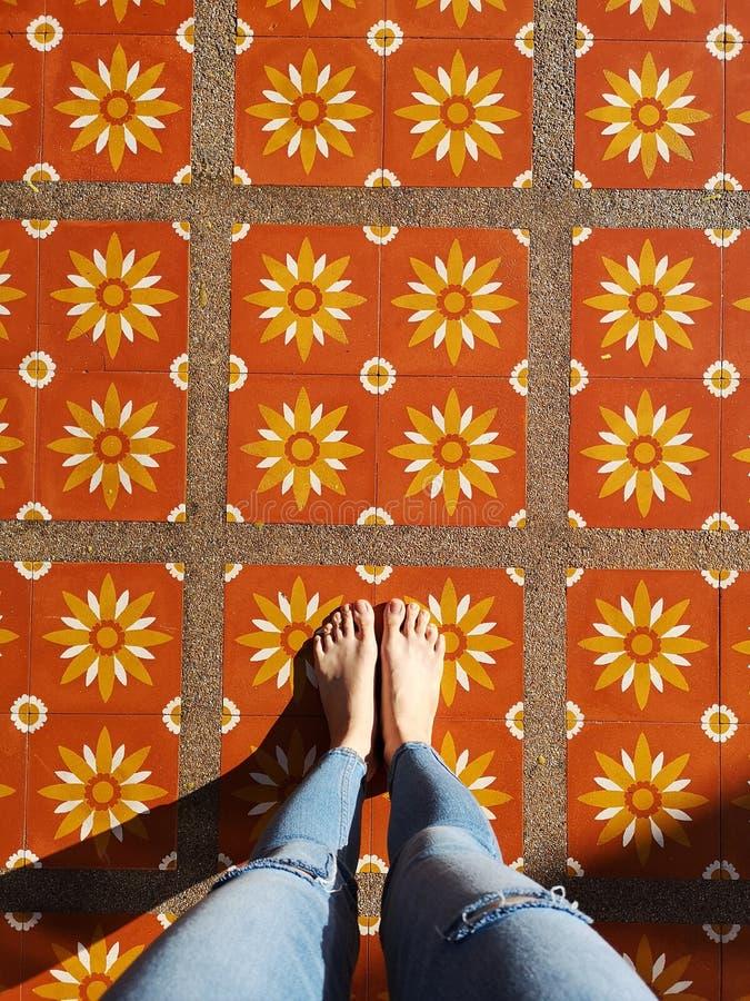 Vista superior Selfie de pies desnudos en suelo de baldosas de la flor Tejanos y pies del desgaste de mujer en Art Copy Space foto de archivo