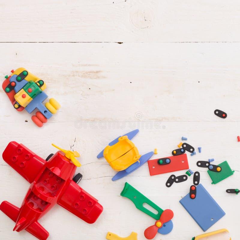 Vista superior sobre ladrillos de juguete coloridos sobre un fondo blanco de madera Juguetes en la mesa fotos de archivo