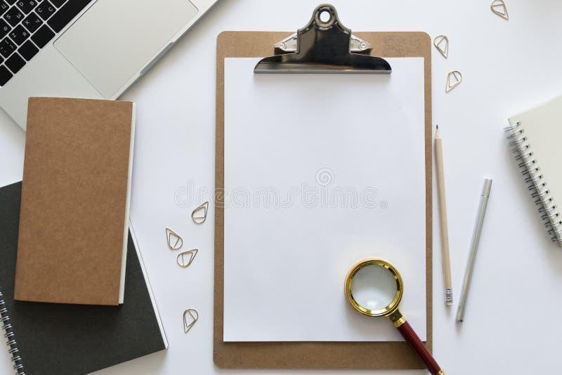 Vista superior sobre a mesa de trabalho com portátil, caderno, lápis, penas e clipes de papel Copie o espaço para o texto Configu fotos de stock royalty free