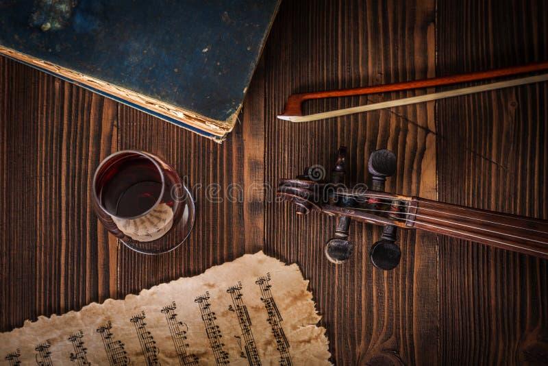 Vista superior sobre o livro velho, o rolo do violino, a curva e a contagem musical foto de stock