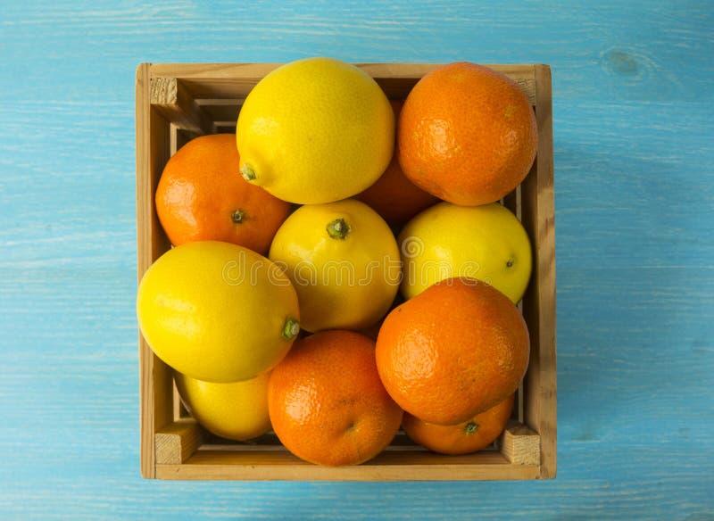 Vista superior Tangerinas e limões frescos em um fundo de madeira Os mandarino e limões em uma caixa de madeira com espaço da cóp fotos de stock
