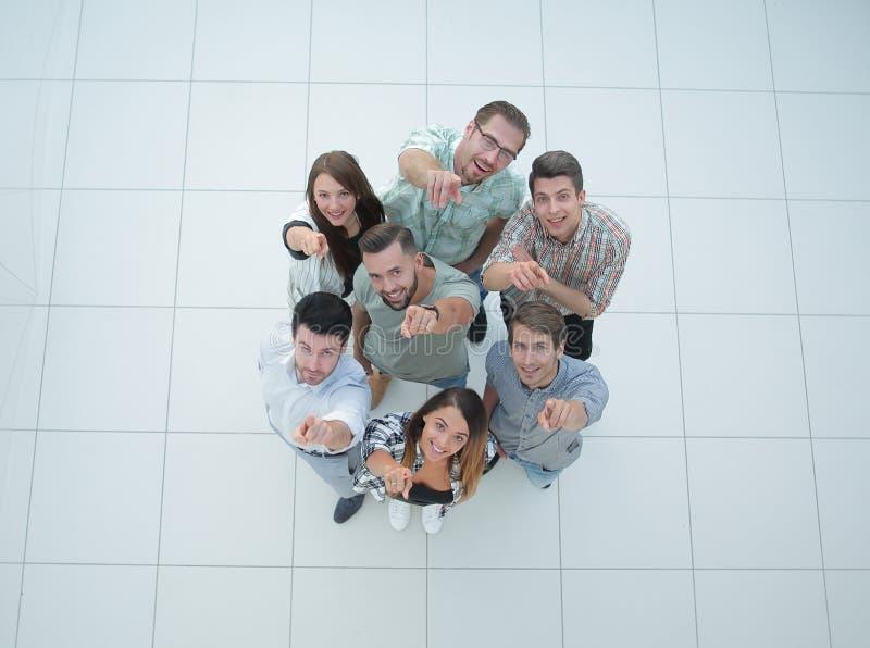 Vista superior um grupo de jovens bem sucedidos que apontam a você fotos de stock