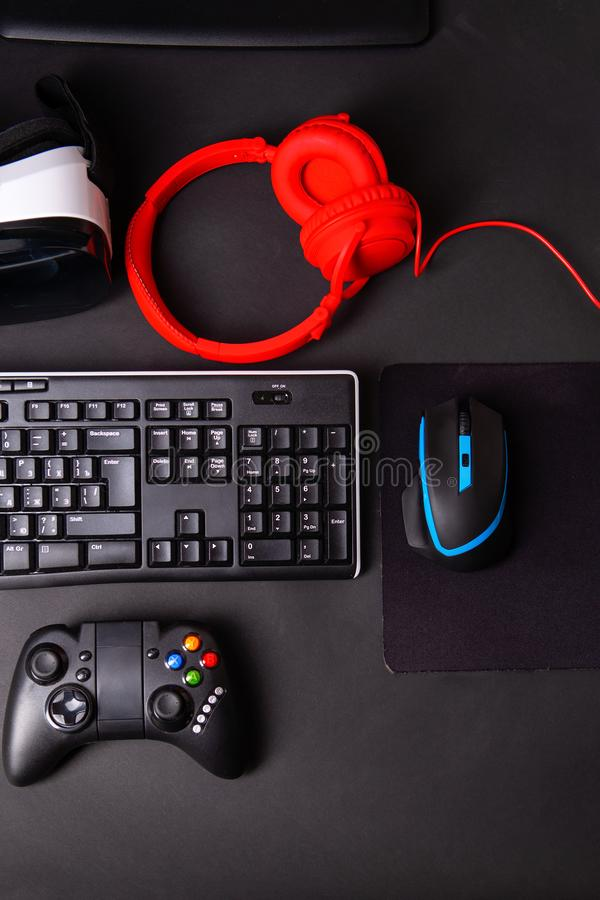 Vista superior uma engrenagem do jogo, rato, teclado, manche, auriculares, auriculares de VR no fundo preto da tabela imagens de stock
