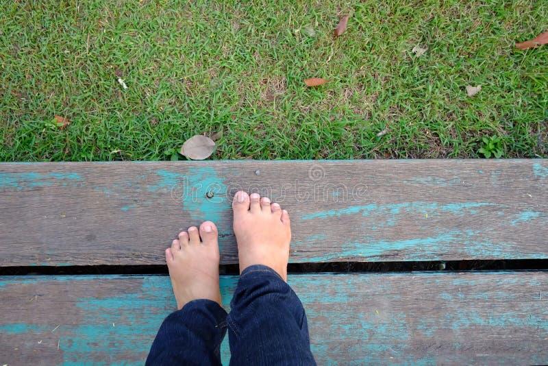 Vista superior uma posição fêmea descalça em um banco de madeira velho com grama verde abaixo do fundo fotografia de stock royalty free