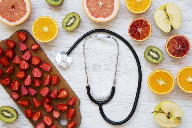 Vista superior, variedade de frutos coloridos diferentes com estetoscópio Conceito da saúde Configuração lisa imagem de stock