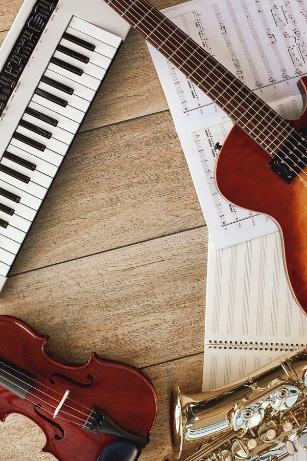 Vista superior vertical de instrumentos musicais diferentes: sintetizador, guitarra, saxofone, violino que encontra-se em folhas  fotos de stock royalty free
