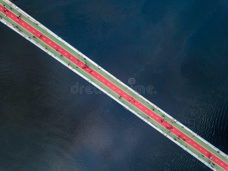 Vista superiore aerea del pedone e del vicolo della pista ciclabile sul ponte del parco e del fiume di Dnieper da sopra nella cit fotografia stock