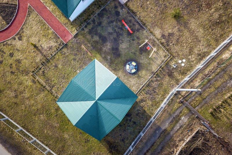 Vista superiore aerea del tetto dell'assicella dell'asilo o dell'edificio scolastico moderno sul campo da giuoco variopinto nel f fotografia stock libera da diritti