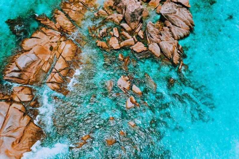 Vista superiore aerea delle onde di oceano che colpiscono le rocce del granito sulla spiaggia in La Digue, Seychelles immagine stock libera da diritti