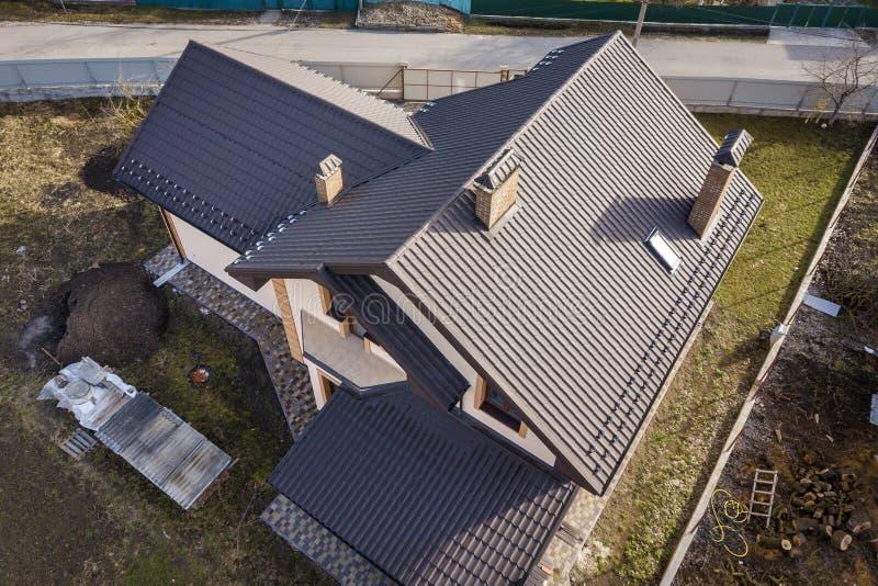Vista superiore aerea di costruzione il tetto ripido dell'assicella, i camini del mattone e di piccola finestra della soffitta su fotografia stock libera da diritti