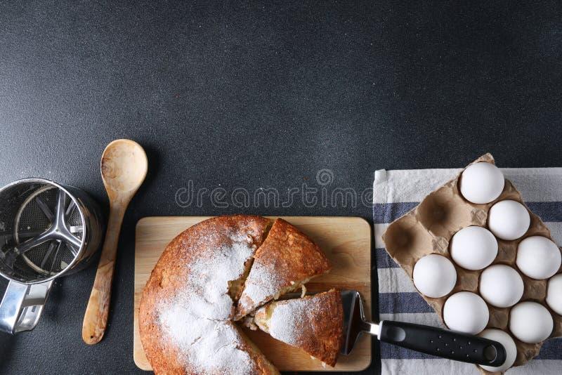 Vista superiore affettata della torta su fondo scuro con gli ingredienti fotografia stock libera da diritti