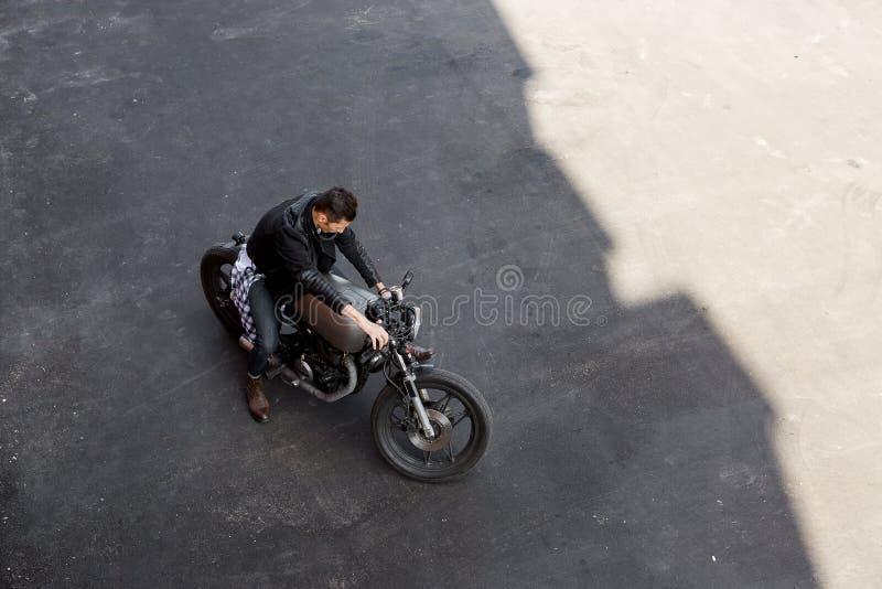 Vista superiore all'uomo brutale con la motocicletta di abitudine del corridore del caffè fotografia stock