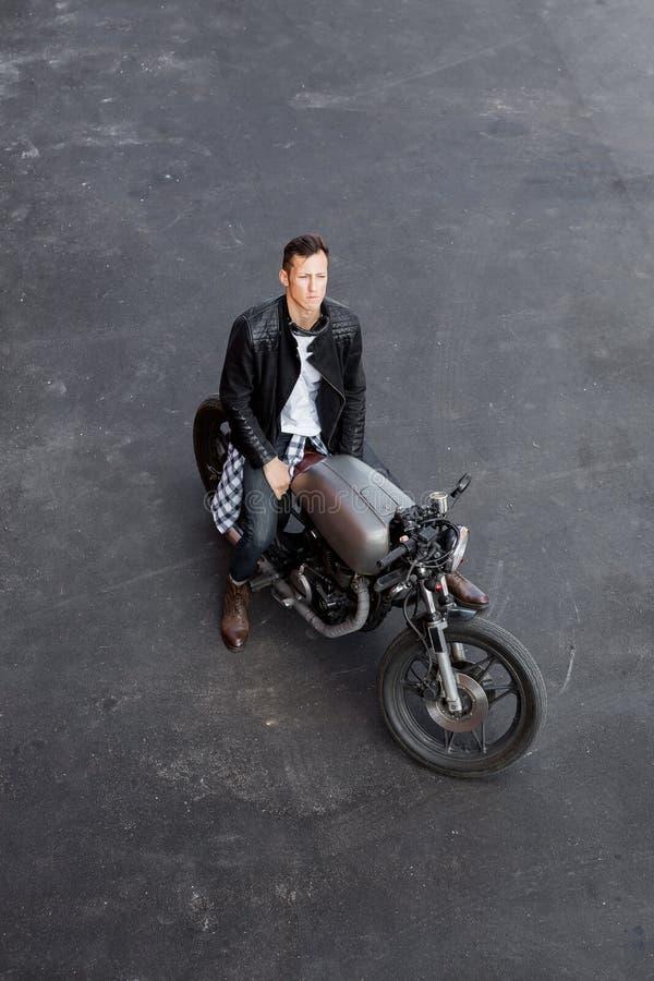 Vista superiore all'uomo brutale con la motocicletta di abitudine del corridore del caffè immagine stock