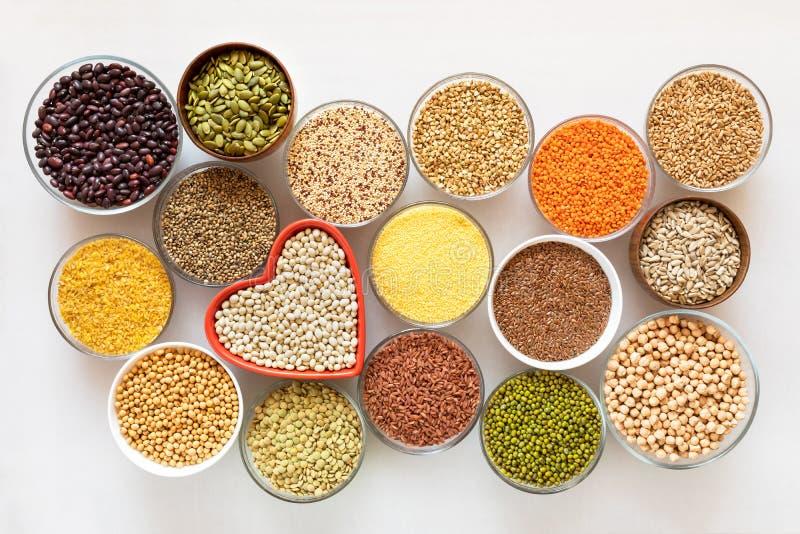 Vista superiore alle ciotole di vetro con i cereali, i fagioli ed i semi con la ciotola in forma di cuore rossa nel mezzo su fond immagine stock libera da diritti
