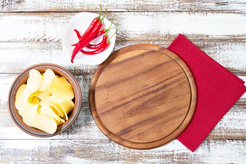 Vista superiore - bordo vuoto dello scrittorio della pizza sulla tavola di legno con peperoncino e le patatine fritte, falsi su fotografie stock libere da diritti