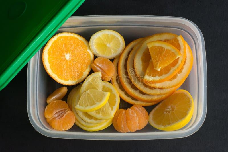 Vista superiore degli agrumi freschi e affettati limone, arancia, mandarino in recipiente di plastica su fondo nero fotografie stock libere da diritti