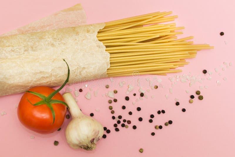 Vista superiore degli ingredienti italiani dei pomodori delle verdure e della pasta, pasta, aglio, pepe, formaggio, spezie su un  immagine stock