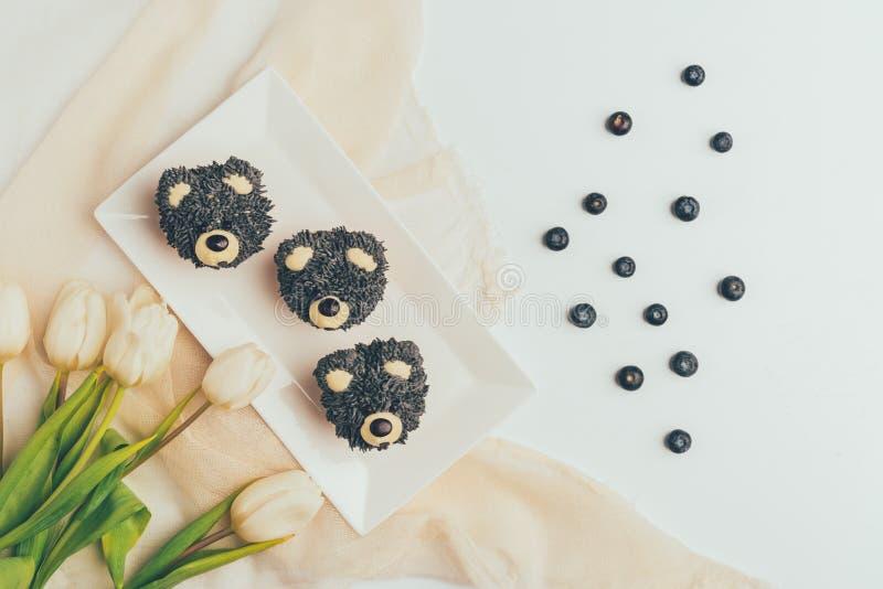 vista superiore dei bigné gastronomici nella forma degli orsi, mirtilli freschi immagini stock libere da diritti