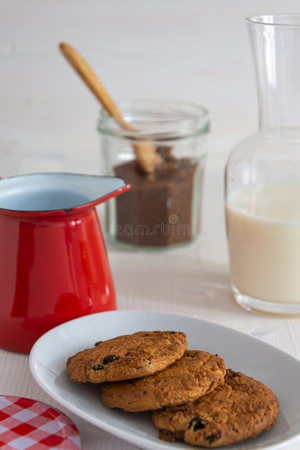 Vista superiore dei biscotti con la bottiglia per il latte, lo zucchero bruno e la casseruola rossa fotografia stock libera da diritti