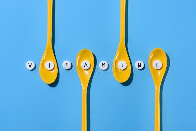 vista superiore dei cucchiai e delle pillole di plastica gialli con l'iscrizione della vitamina nella fila immagine stock