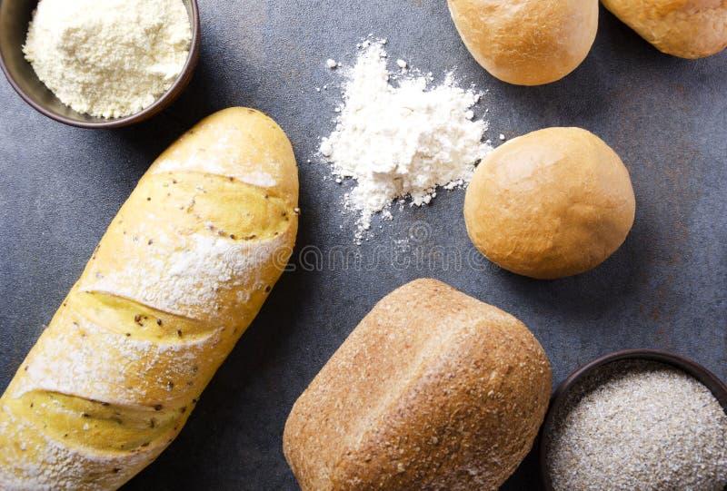 Vista superiore dei generi differenti di pane, ciotole con farina su superficie rustica grigia Concetto del varius dei prodotti d immagine stock libera da diritti