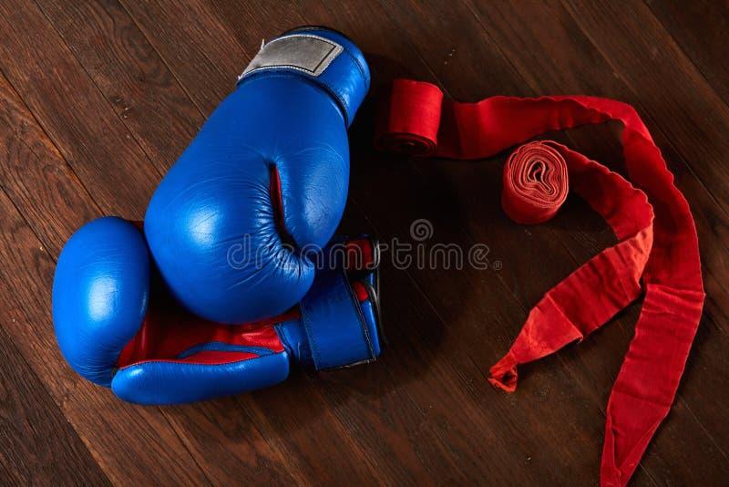 Vista superiore dei guantoni da pugile e della fasciatura blu e rossi sul fondo di legno della plancia immagini stock