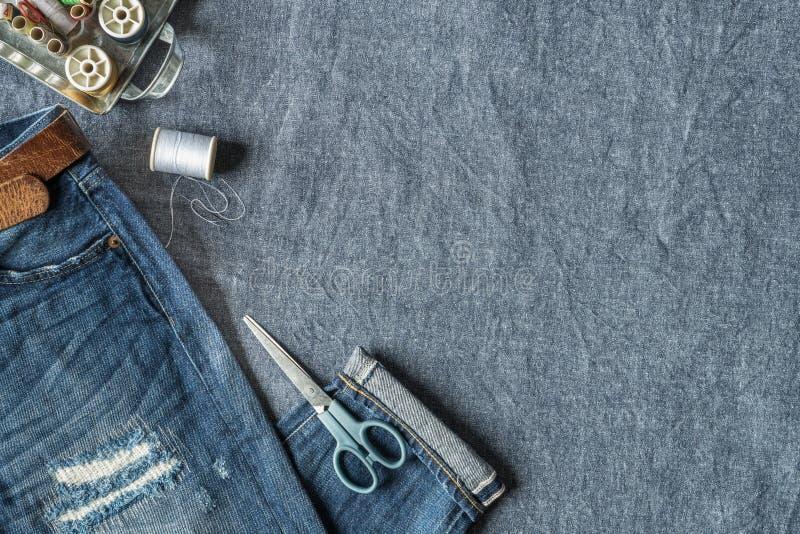 Vista superiore dei jeans nocivi e degli strumenti di cucito fotografie stock