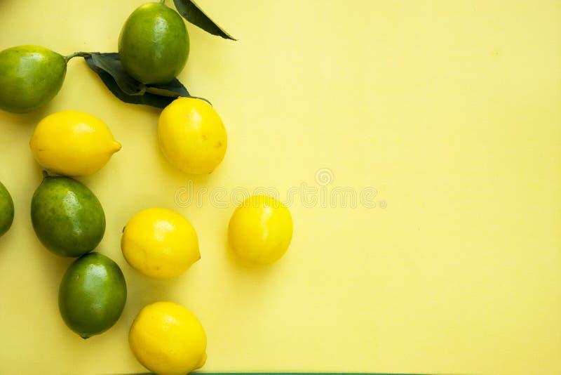 Vista superiore dei limoni gialli e verdi variopinti su fondo pastello giallo, concetti, idee di estate di frutta, di verdure fotografia stock