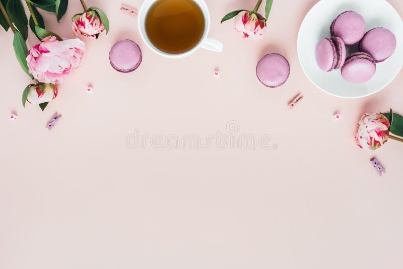 Vista superiore dei maccheroni con una tazza di tè e delle peonie fotografie stock