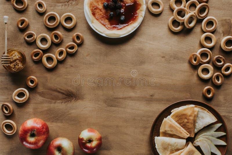 vista superiore dei pancake deliziosi con le bacche miele e bagel delle mele immagine stock