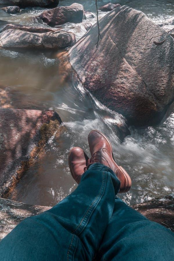 Vista superiore dei piedi con le vecchie scarpe marroni ed il tralicco blu sulla pietra al bordo del fiume immagini stock