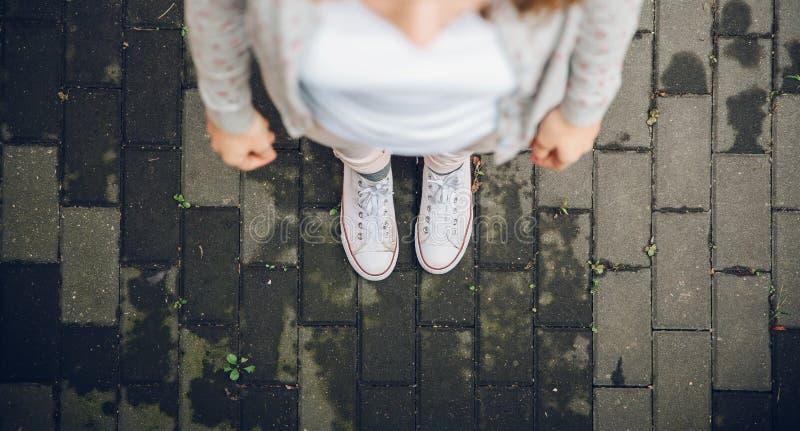 Vista superiore dei piedi della donna in scarpe da tennis bianche all'aperto immagine stock libera da diritti