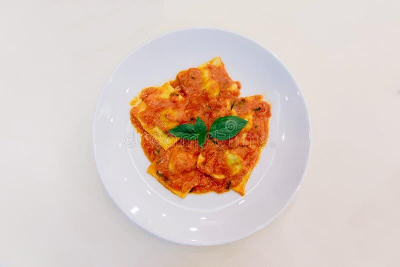 Vista superiore dei ravioli con salsa al pomodoro e del basilico in piatto bianco sulla tovaglia bianca immagini stock