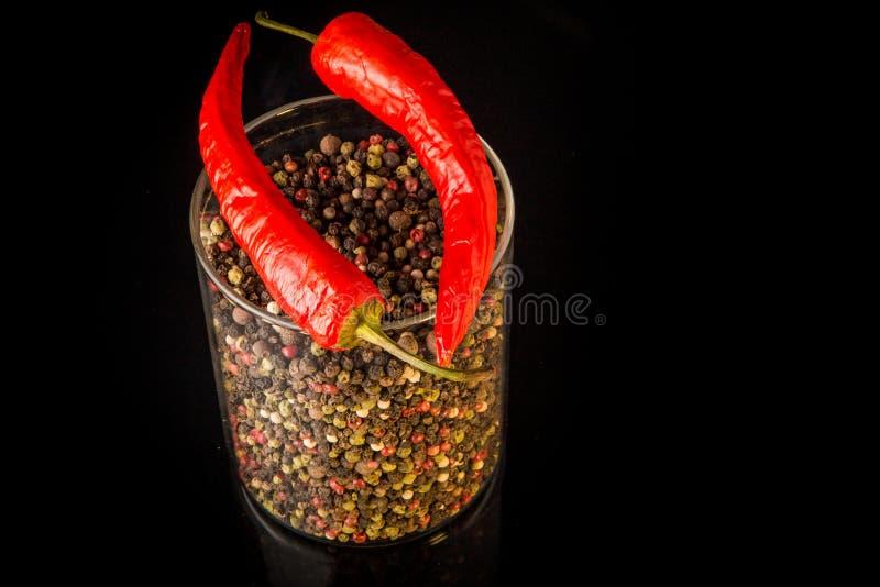 vista superiore del barattolo di vetro alto con i granelli di pepe e l'intero peperoncino rosso due immagine stock