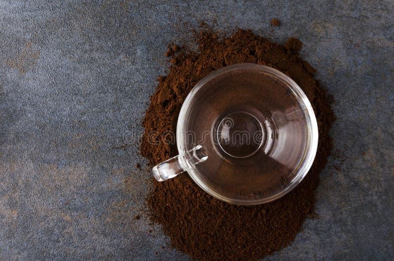 Vista superiore del caffè macinato del mucchio, tazza di vetro sulla tavola scura tazza di caffè che veste bianco di mattina dell fotografia stock libera da diritti