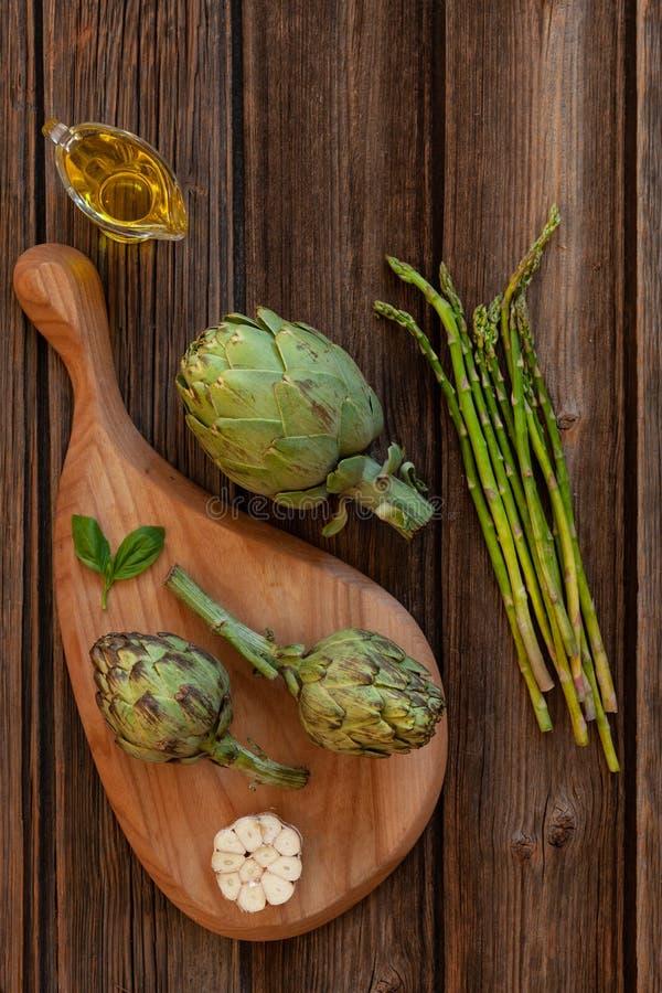 Vista superiore del carciofo fresco e mazzo di asparago verde con aglio e olio d'oliva sulla tavola di legno immagine stock